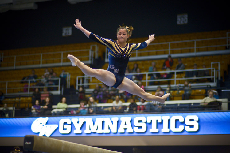 Liz Pfeiler leaps in to the air during her performance on the balance beam, which earned her a team-high score of 9.80.